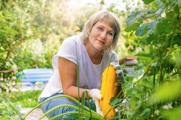 Une femme jardine dans l'arrière-cour de sa maison