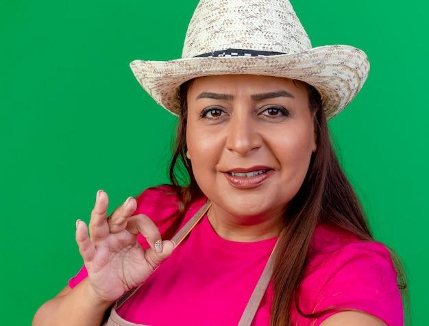 Femme de jardinier d'âge moyen en tablier et chapeau montrant signe ok