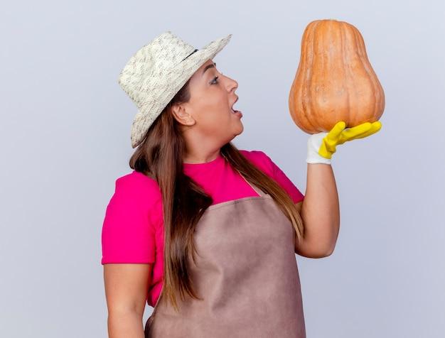 Femme de jardinier d'âge moyen en tablier et chapeau portant des gants en caoutchouc tenant la citrouille en regardant surpris debout sur fond blanc