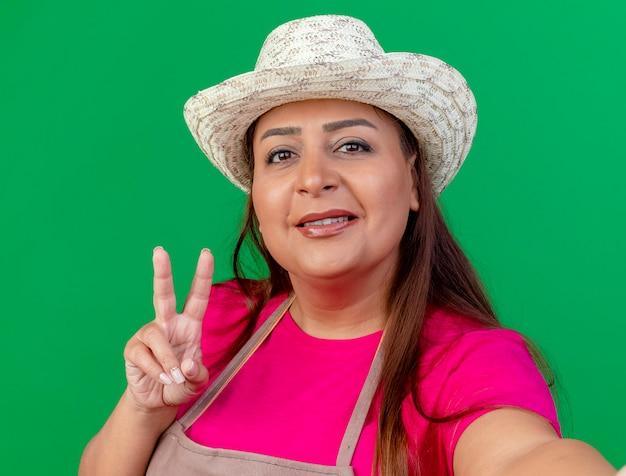 Femme de jardinier d'âge moyen en tablier et chapeau souriant