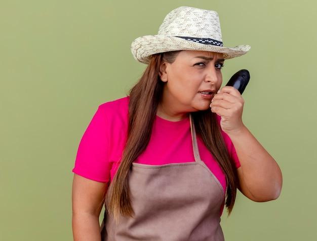 Femme de jardinier d'âge moyen en tablier et chapeau tenant des aubergines fraîches avec visage en colère