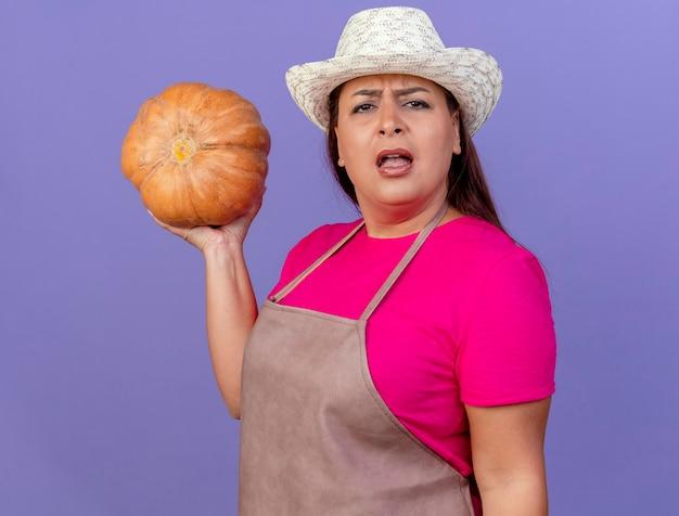 Femme de jardinier d'âge moyen en tablier et chapeau tenant la citrouille regardant la caméra avec un visage sérieux debout sur fond violet