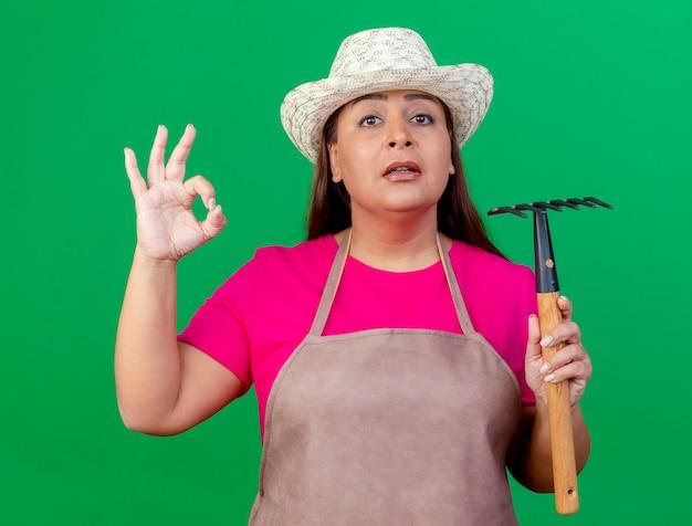 Femme de jardinier d'âge moyen en tablier et chapeau tenant un mini râteau