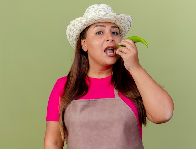 Femme de jardinier d'âge moyen en tablier et chapeau tenant le piment vert