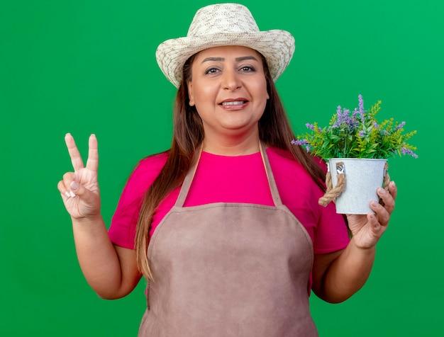 Femme de jardinier d'âge moyen en tablier et chapeau tenant en pot