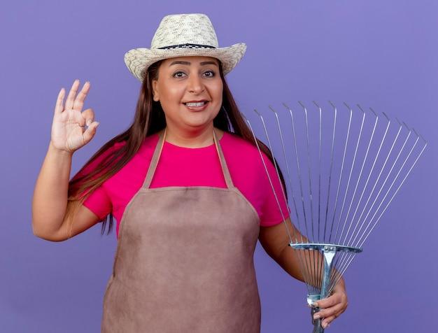 Femme de jardinier d'âge moyen en tablier et chapeau tenant râteau souriant montrant signe ok