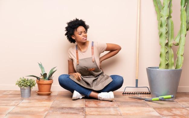 Femme jardinier assis sur le sol autour des plantes