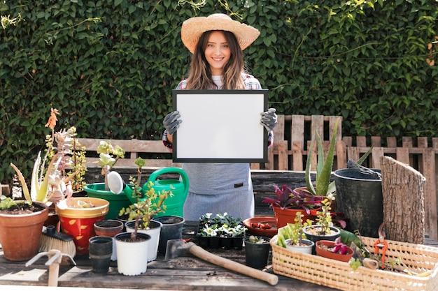 Femme jardinier debout derrière les plantes en pot montrant un cadre blanc