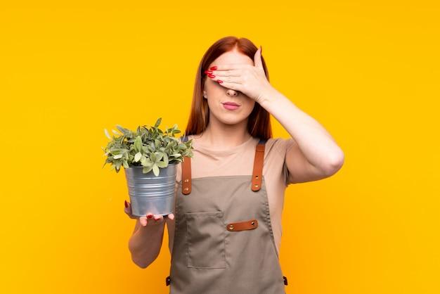 Femme jardinier jeune rousse tenant une plante couvrant les yeux par les mains