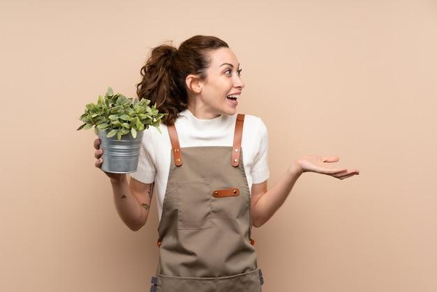Femme jardinier tenant une plante avec une expression faciale surprise