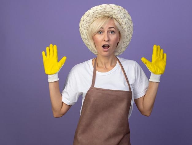 Femme jardinière blonde d'âge moyen impressionnée en uniforme portant un chapeau et des gants de jardinage montrant les mains vides