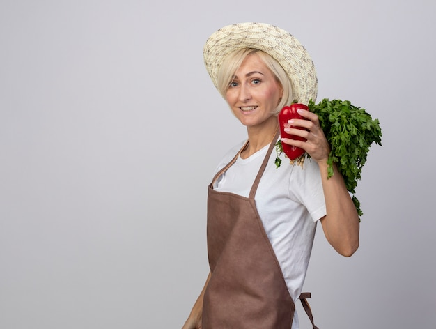 Femme jardinière blonde d'âge moyen souriante en uniforme portant un chapeau debout en vue de profil tenant un bouquet de coriandre et de poivre regardant à l'avant isolé sur un mur blanc avec espace de copie