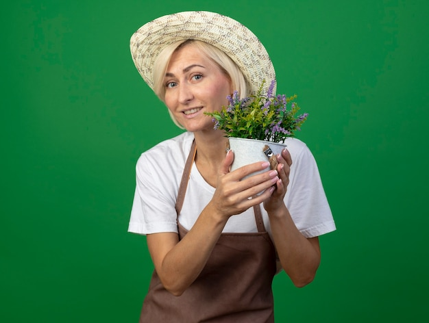 Femme jardinière blonde d'âge moyen souriante en uniforme portant un chapeau tenant un pot de fleurs