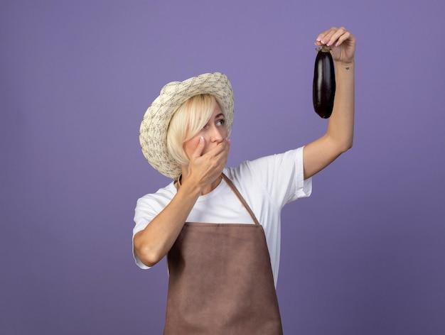 Femme jardinière blonde d'âge moyen en uniforme portant un chapeau soulevant une aubergine en la regardant en gardant la main sur la bouche isolée sur un mur violet avec espace de copie