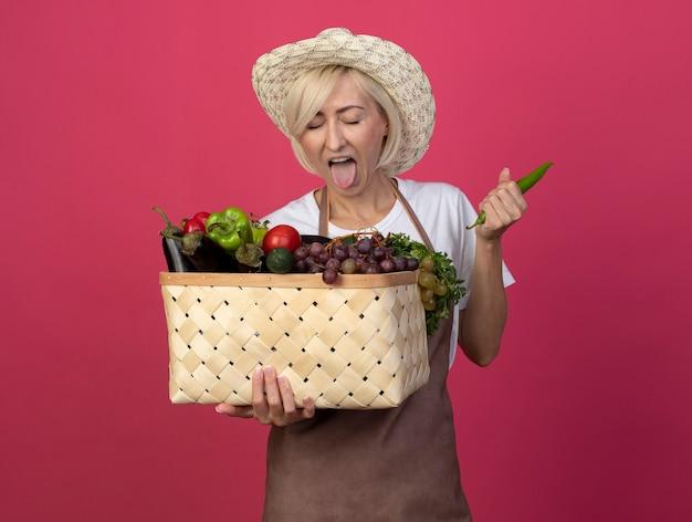 Femme jardinière blonde d'âge moyen en uniforme portant un chapeau tenant un panier de légumes et de poivre montrant la langue avec les yeux fermés