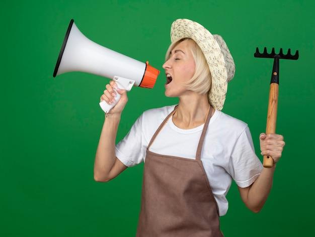 Femme jardinière blonde d'âge moyen en uniforme portant un chapeau tenant un râteau parlant par le haut-parleur avec les yeux fermés tenant un râteau