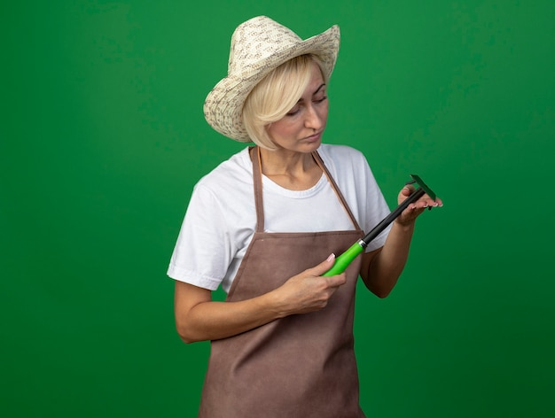 Femme jardinière blonde d'âge moyen en uniforme portant un chapeau tenant et regardant un râteau-houe