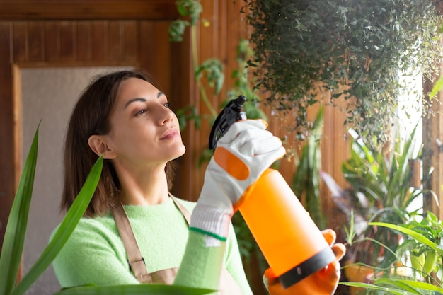 Femme jardinière à la maison en tablier et gants avec des plantes en croissance sur le balcon de la maison arrosant à l'aide d'un spray