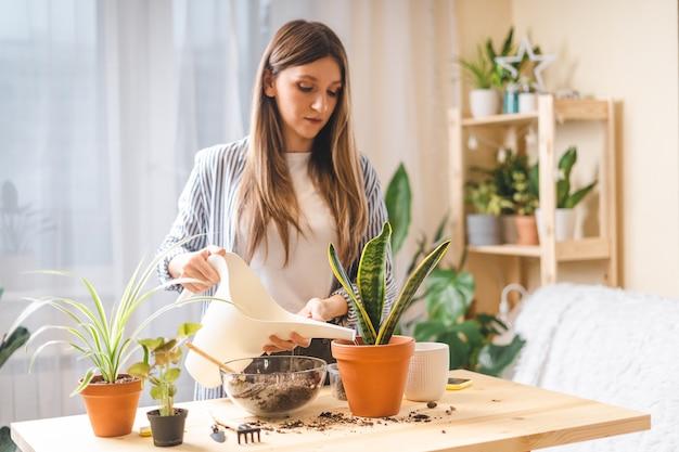 Femme jardiniers arrosage plante