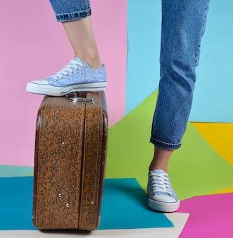 Femme avec un jean et des baskets devient un pied sur une valise rétro sur un mur de papier multicolore