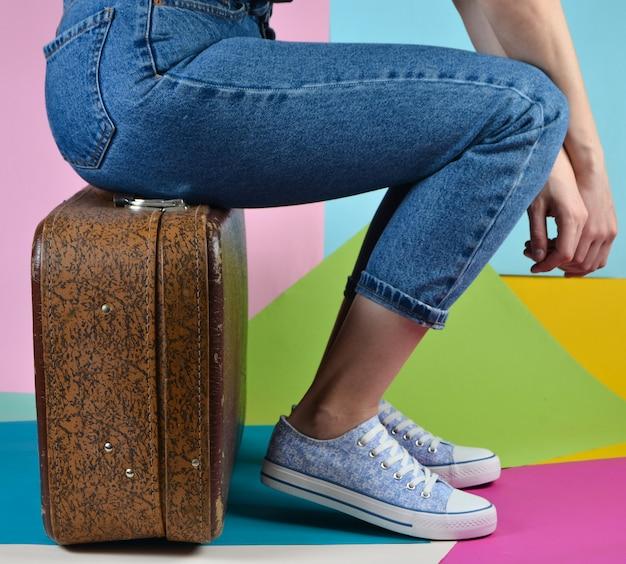 Femme avec un jean et des baskets est assis sur une valise rétro sur mur de papier multicolore