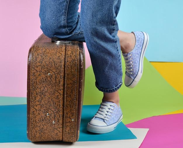 Femme avec un jean et des baskets prend son genou sur une valise rétro sur un mur de papier multicolore