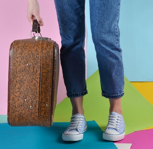 Femme avec un jean et des baskets tenant dans sa main valise rétro sur mur de papier multicolore