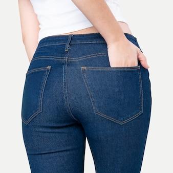 Femme en jean bleu avec la main rentrée dans la poche photoshoot de mode vue arrière