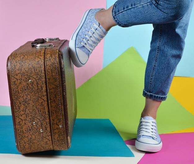 Femme avec un jean roulé et des baskets pousse une valise rétro sur un mur de papier multicolore