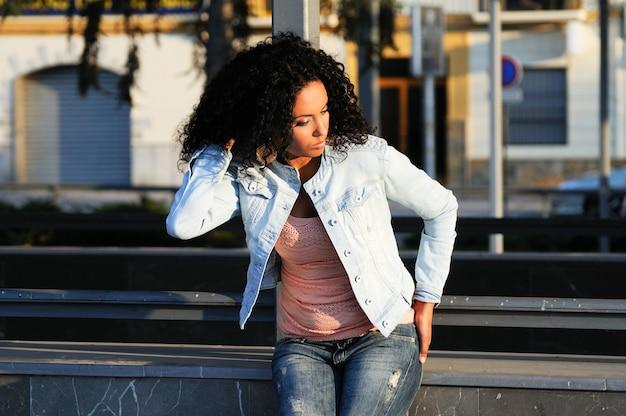 Femme en jeans assis dans la rue