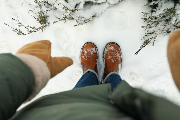 Femme en jeans et bottes debout en plein air en hiver