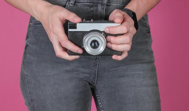 Femme en jeans est titulaire d'un appareil photo argentique rétro sur fond rose. recadrer la photo