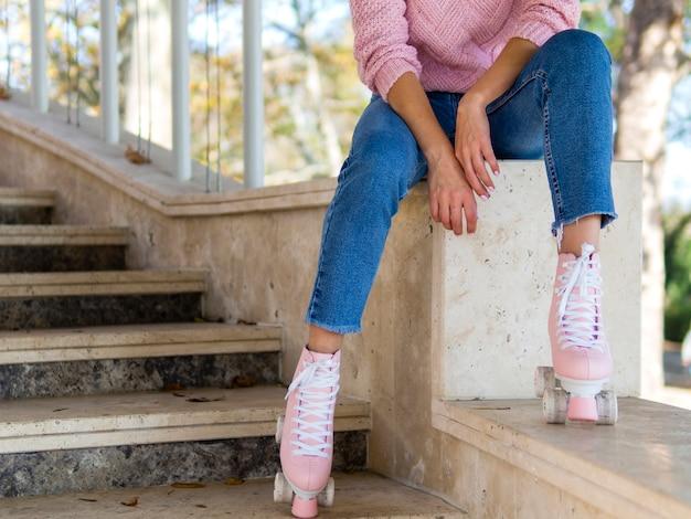 Femme en jeans posant avec des patins à roulettes dans les escaliers