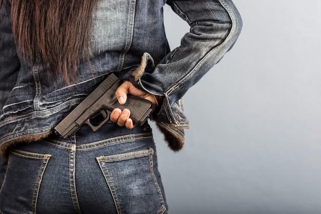 Une femme en jeans tient une arme à la main.