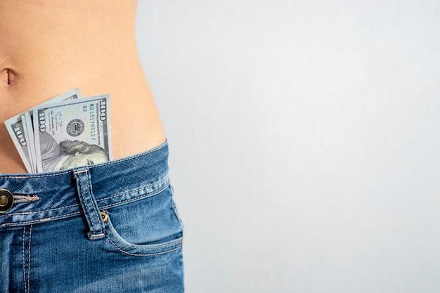 Une femme en jeans avec un ventre nu avec des dollars qui sortent de son pantalon. le concept de striptease. copiez l'espace.