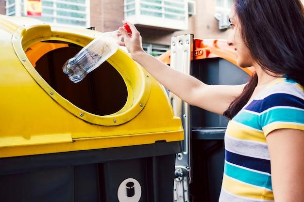 Femme jetant une bouteille dans un bac de recyclage