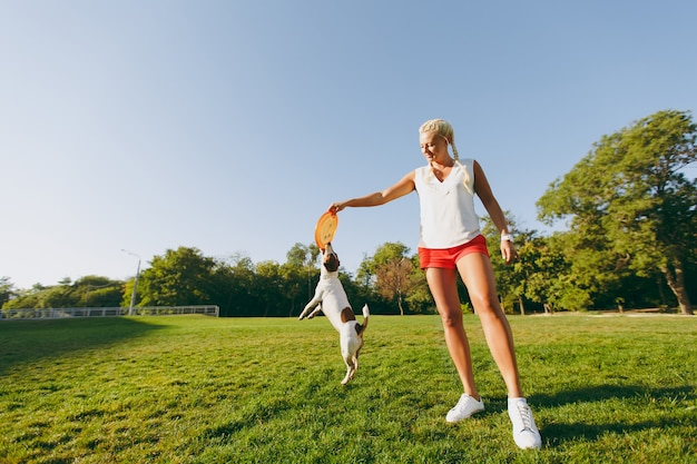 Femme jetant un disque volant orange à un petit chien drôle, qui l'attrape sur l'herbe verte. little jack russel terrier animal jouant à l'extérieur dans le parc. chien et propriétaire en plein air.
