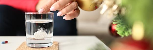 Femme jetant une pilule soluble effervescente dans un verre d'eau à la maison près de l'arbre de noël gros plan