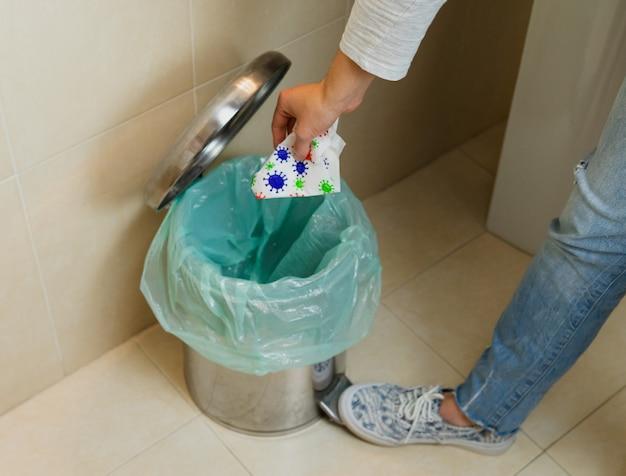 Femme jetant une serviette avec le virus dans la poubelle. concept covid-19. coronavirus.