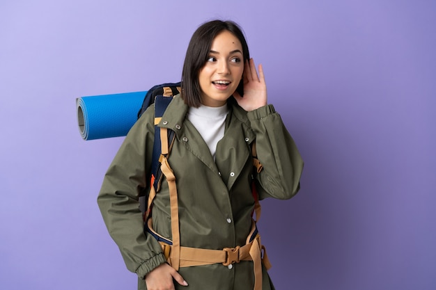 Femme jeune alpiniste avec un gros sac à dos en écoutant quelque chose en mettant la main sur l'oreille