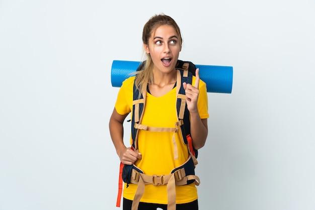 Femme jeune alpiniste avec un gros sac à dos isolé sur fond blanc pensant une idée pointant le doigt vers le haut