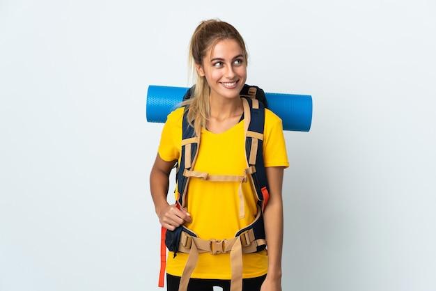 Femme jeune alpiniste avec un gros sac à dos isolé sur fond blanc en pensant à une idée tout en levant