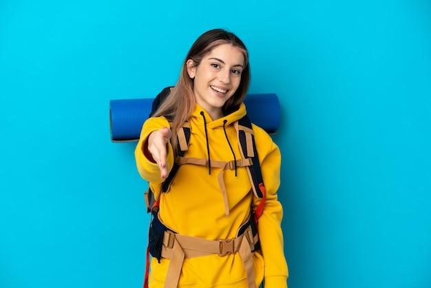 Femme jeune alpiniste avec un gros sac à dos isolé