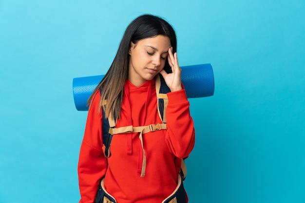 Femme jeune alpiniste avec sac à dos avec maux de tête