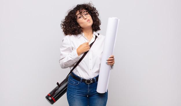 Femme jeune architecte haussant les épaules, se sentant confus et incertain, doutant des bras croisés et regard perplexe