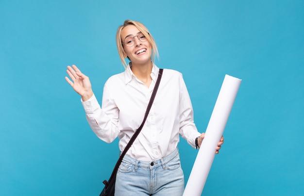 Femme jeune architecte souriant joyeusement et gaiement, en agitant la main, en vous accueillant et en vous saluant, ou en vous disant au revoir