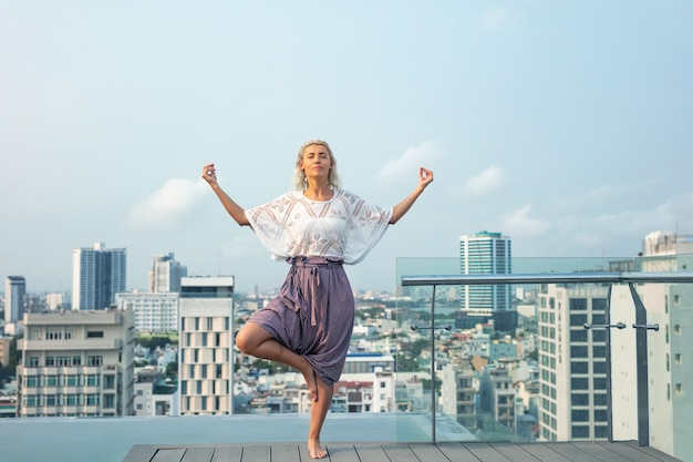 Femme jeune belle sur le toit de l'hôtel au bord de la piscine avec vue sur la ville