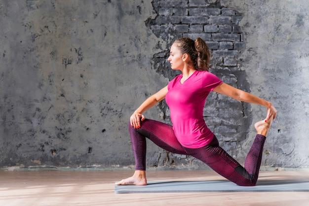 Femme jeune en bonne santé, faire du yoga dans une salle de sport