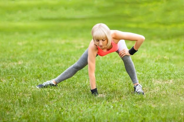 Femme jeune en bonne santé qui s'étend avant la remise en forme et l'exercice