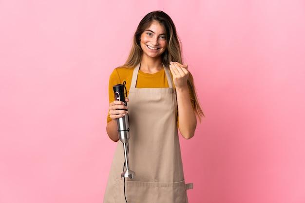 Femme jeune chef à l'aide d'un mélangeur à main isolé